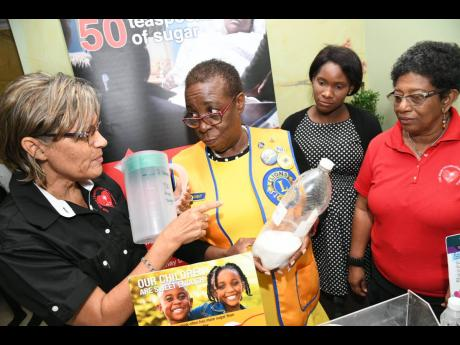 From left: Debbie Chen, executive director of the Heart Foundation of Jamaica, in discussion with from Julette Parkes-Livermore, president of Lions Club of Kingston, and members Sandrice White and Kay Cooke about the debate on the consumption of sugary drinks and the call for lifestyle changes to reduce obesity in the island at the Lions Club lunch meeting at the Courtleigh Hotel in New Kingston yesterday.