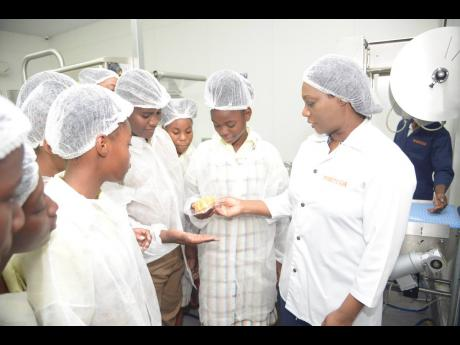 Florence Reid (right), head of manufacturing at Tortuga, shares a few insights on the sealing process for Tortuga cakes with a few Camperdown High School students during a tour of the baking facility in Cross Roads, Kingston, on Tuesday, May 21, 2019. The tour was part of an education outreach initiative by the Jamaica Stock Exchange.