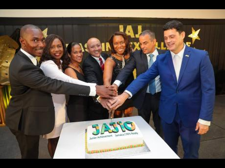 Members of the board of Junior Achievement Jamaica celebrate a proud moment as they cut the 10th-anniversary cake of the organisation. From left are Chaluk Richards of GK General Insurance Company Limited; Deloris Jones of JN Fund Managers Limited; Caribbean Broilers' Alicia Bogues and Matthew Lyn; Alphie Mullings-Aiken of JA Jamaica; Paul Lalor of the Insurance Company of the West Indies; and Emanuel DaRosa of the Jamaica Public Service Company Limited.