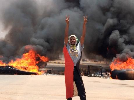 A protester flashes the victory sign in front of burning tires and debris on Road 60, near Khartoum's army headquarters, in Khartoum, Sudan, on Monday, June 3. Sudanese protest leaders say at least 13 people have been killed on Monday in the military's assault on the sit-in outside the military headquarters. The protesters have announced that they are suspending talks with the military regarding the creation of a transitional government.