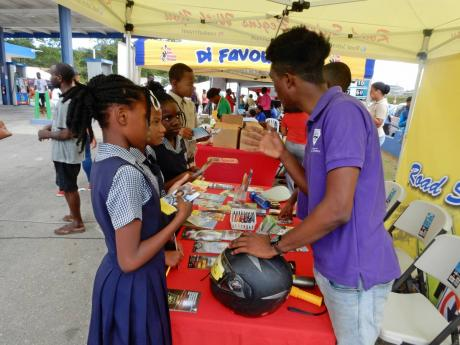 Primary-school students seeking information at the road-safety booth in Golden Grove, St Ann, on Wednesday.