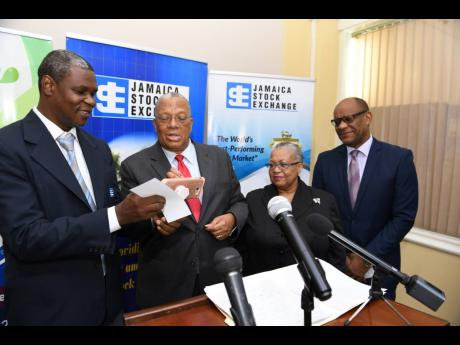 Neville Ellis (left), marketing and communications manager of the Jamaica Stock Exchange, assists Opposition Leader Dr Peter Phillips to ring the bell, using a smartphone, to indicate the start of the day's trading at the JSE yesterday. Looking on are Marlene Street Forrest (second right), managing director of the stock exchange, and Ian McNaughton, chairman.
