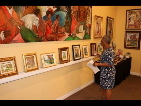 Jamaica's Central Labor, Chief Liaison Officer, Mrs Mettie Scarlett-Jones, browses through the art collection on display at the Embassy of Jamaica in Washington D.C., mounted by Jamaican artists Paul Blackwood and Courtney Morgan.