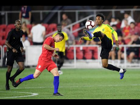 Jamaica midfielder Tyreek Magee (right) acrobatically traps the ball before being challenged by United States midfielder Wil Trapp (middle) during the second half of their international friendly match at Audi Field in Washington DC on Wednesday night. Jamaica won 1-0.