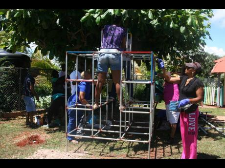 Kiwanis volunteers preparing playground equipment for installation on the grounds of the Junction Women Centre in St Elizabeth. The equipment came courtesy of the Kiwanis Division 25 (Cornwall) under its 'Playground Effect' project.