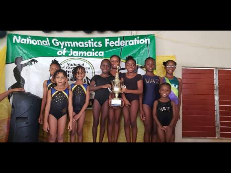 St Theresa Prep's gymnasts stand on the first-place podium with their trophy won at the Jamaica Amateur Gynmastics Association's All-Island Schools Competition, held at the Pembroke Hall Methodist Church Hall on Saturday, June 1. Joining them on the podium are Mavisville Prep (left) and Vaz Prep.