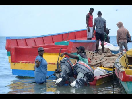 Fisherwoman Shernette Douglas (left) gets assistance from other fishermen in Rocky Point, Clarendon, to load and prepare her boat for sea yesterday.