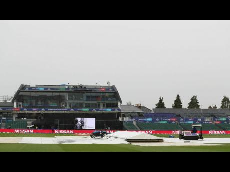 Ground staff work to clear water off the outfield prior to the ICC Cricket World Cup match between Pakistan and Sri Lanka, at Bristol County Ground, in Bristol, England yesterday.
