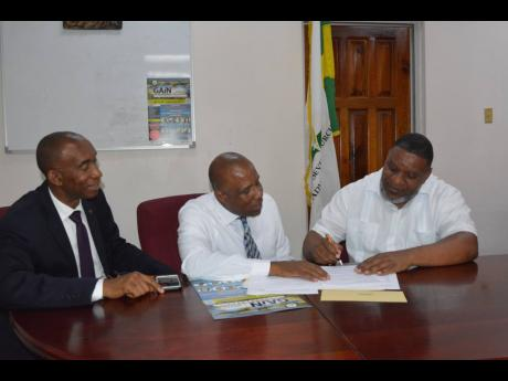 Owner of Three Angels pharmacy, Rohan McNellie (right), signs the sponsorship agreement in support of the GAiN Jamaica Conference scheduled for July 4-6 at the Iberostar Rose Hall Beach hotel in Montego Bay. Witnessing the signing are Dr Meric Walker (left), executive secretary of the Jamaica Union Conference of Seventh-day Adventists and Nigel Coke, communication director of the Adventist Church in Jamaica