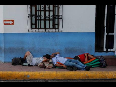 Migrants sleep on a sidewalk in Tapachula, Chiapas state, Mexico, on Saturday.