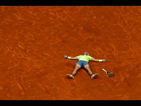 An outstretched Rafael Nadal of Spain celebrates his record 12th French Open tennis tournament title after winning his men's final match against Austria's Dominic Thiem in four sets, 6-3, 5-7, 6-1, 6-1, at the Roland Garros Stadium in Paris, France, yesterday.