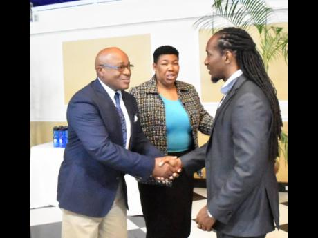 State Minister in the Ministry of Education, Youth and Information Alando Terrelonge (right) is greeted by Commissioner of Corrections, Lieutenant Colonel (Ret) Gary Rowe on his arrival at the Terra Nova All-Suite Hotel in St Andrew on June 5 for the Department of Correctional Services' appreciation luncheon for teachers and instructors serving in the penal system. Sharing the moment is Deputy Commissioner Joyce Stone.