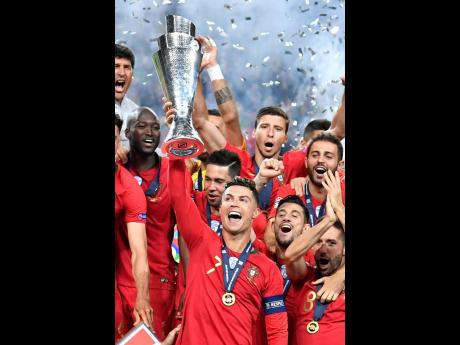 Portugal's Cristiano Ronaldo raises the trophy as he celebrates with his teammates after winning the UEFA Nations League final against the Netherlands at the Estádio do Dragão in Porto, Portugal yesterday.