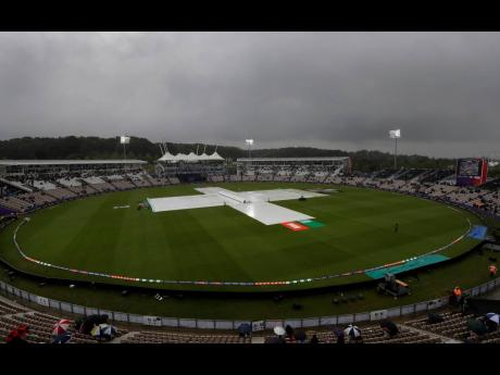 Rain covers on the pitch after play was stopped due to rain during the ICC World Cup match between South Africa and the Windies at The Ageas Bowl in Southampton, England yesterday. (AP Photo/Kirsty Wigglesworth)