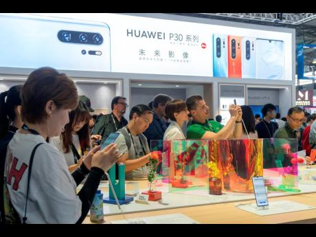 Visitors look at a display of smartphones from Chinese technology firm Huawei at the Consumer Electronics Show in Shanghai on Tuesday, June 11.