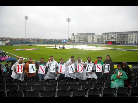 Bangladesh cricket fans display their allegiance as they stand in the rain during the ICC Cricket World Cup group-stage match at the County Ground in Bristol, England, yesterday. Bangladesh were scheduled to play Sri Lanka yesterday,  but the match was rained out.