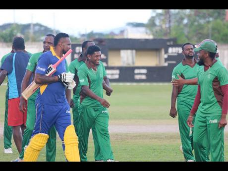 Captain Krishmar Santokie (third left) is congratulated by teammates following Clarendon's win over St Elizabeth in the Jamaica Cricket Association T20 Bashment tournament at Chedwin Park, St Catherine, at the weekend.