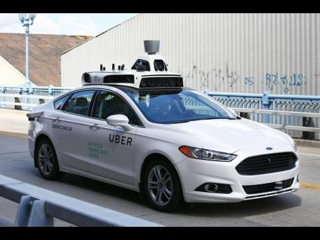 A self-driving Ford Fusion hybrid car is seen being test-driven on August 18, 2016, in Pittsburgh.