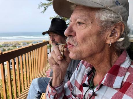 AP Photos right: In this April 25, 2019 photo, two-time cancer survivor and medical marijuana cardholder Bill Blazina, 73, smokes a marijuana joint on the deck of his neighbour's home in Waldport, Oregon.