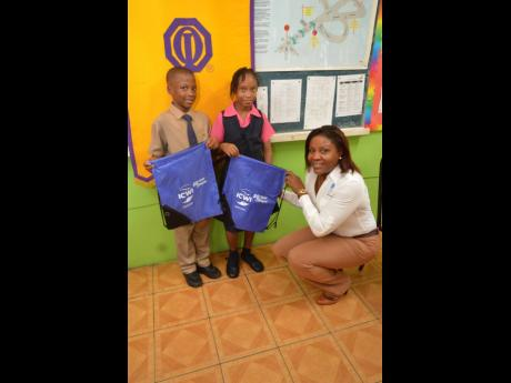 Vice President of finance at the Insurance Company of the West Indies, Sandra Johnson presents grade four students of the New Providence Primary School Rasheed Tucker (left) and Natassia Bright with gift bags. Members of the insurance company visited the school on Wednesday, May 29 as a part of the road safety campaign which seeks to reach and educate as many young individuals on how to use the roadways safely.