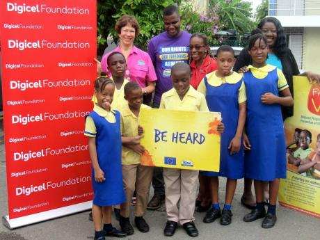 Children supported by the Digicel Foundation have fun while posing for their picture with (back row, from left): Sonita Abrahams, executive director, RISE Life Management Services; Shawn McGregor, programme manager, RISE Life Management Services; Jennifer Spence-Silvera, programme manager/education and special needs, Digicel Foundation; and Juliet Campbell McPherson, principal, St Michael's Primary School in Kingston.