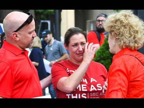 Jules Woodson (centre) of Colorado Springs, Colorado, is comforted by her boyfriend Ben Smith (left) and Christa Brown while demonstrating outside the Southern Baptist Convention's annual meeting on Tuesday, June 11, in Birmingham, Alabama. First-time attendee Woodson spoke through tears as she described being abused sexually by a Southern Baptist minister.