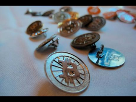 Bitcoin buttons are displayed on a table at the Inside Bitcoins conference in Berlin, on February 12, 2014.