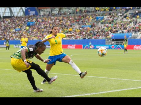 Jamaica's Trudi Carter (left) whips in a cross before Brazil's Thaisa can put in a leg to block it during their opening match in Group C of the FIFA Women's World Cup at the Stade des Alpes in Grenoble, France on Sunday.