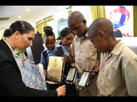 Suzanne Stanley, CEO of JET, examines the plaques of champion school, Holland Primary, students (from second left) Shaquira Milton Jahnnani Brown, Shevaughn Ebanks and Jaden Newland at the 2019 Schools' Environment Programme Research Day and Awards Ceremony at The Knutsford Court Hotel in New Kingston on Wednesday. Rudolph Brown/Photographer