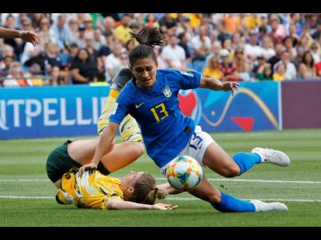 Brazil's Leticia Santos (right) falls inside the Australian box after being tackled by Australia's Elise Kellond-Knight during their Group C FIFA Women's World Cup match at Stade de la Mosson in Montpellier, France, yesterday.