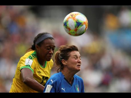 Italy's Cristiana Girelli (right) jumps for the ball with Jamaica's Allyson Swaby during their FIFA Women's World Cup Group C match at the Stade Auguste-Delaune in Reims, France, this morning.