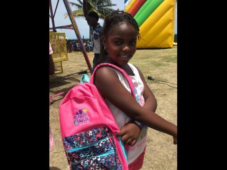 A student shows off her Purple Slush bag pack at a previous Purple Slush Fun Day