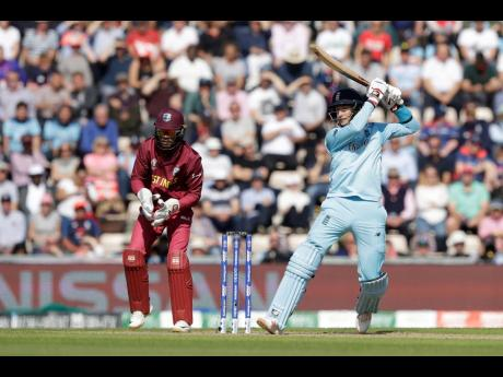 England's Joe Root hits a four while Windies wicketkeeper Shai Hope looks on during their ICC Cricket World Cup match at the Hampshire Bowl in Southampton, England, yesterday.