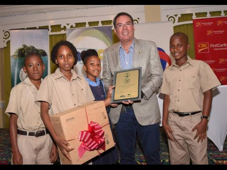 Minister without Portfolio in the Ministry of Economic Growth and Job Creation Daryl Vaz (second right) with members of the winning team from Holland Primary School in the Schools' Environment Programme (SEP) competition (from left): Jaden Newland, Jahmani Brown, Shaqira Milton and Shevaughn Ebanks. The occasion was the SEP Research Day and Awards Ceremony held on June 12 at The Knutsford Court Hotel in Kingston.