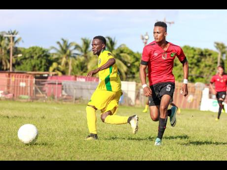 Renior Elliott (left) of Vere FC battles with Downs FC's Romario Witter during their JFF All-Island Confederation Play-Offs encounter at the Wembley Centre of Excellence in Hayes, Clarendon, on Sunday, June 3.