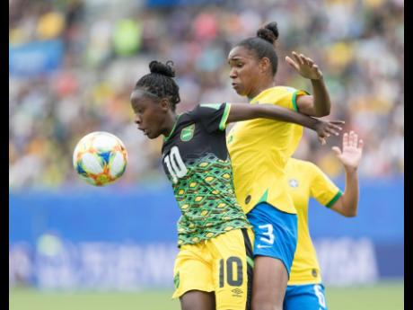 Jamaica's Jody Brown holds off the challenge of Brazil's Érika to take control of the ball during their match in the FIFA Women's World Cup at the Stade des Alpes in Grenoble, France, on Sunday June 9. Brown, 17 years old, is the youngest Reggae Girl at the FIFA Women's World Cup.