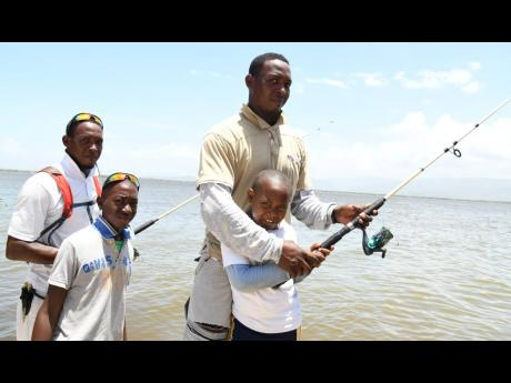 From left: Georzinno Gayle and son Jerzinno and Jaylon Gayle and son Jayquan  fish along the old Causeway bridge on Father's Day yesterday.