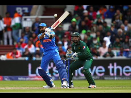 India captain Virat Kohli plays a shot under the watch of Pakistan wicketkeeper-captain Sarfaraz Ahmed during their ICC World Cup match at Old Trafford in Manchester, England, yesterday.