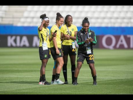 National senior women's football team player Kayla McCoy (second left) shares a joke with teammates (from left) Deneisha Blackwood, Olufolasade Adamolekun and Mireya Grey during a familiarisation tour of the Stade Auguste-Delaune in Reims, France, last Thursday ahead of the team's second FIFA Women's World Cup match against Italy.