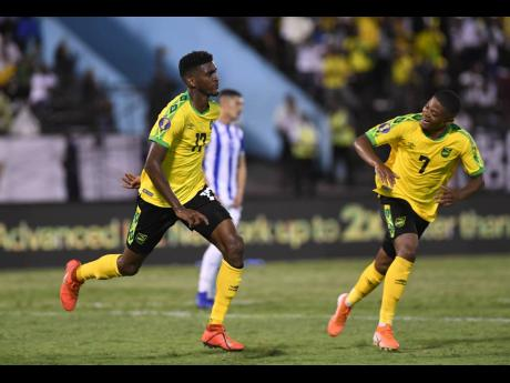 Jamaica's Damion Lowe (left) runs off in celebration with teammate Leon Bailey after netting the team's third goal in their 3-2 win over Honduras in their Group C clash in the Concacaf Gold Cup at the National Stadium tonight.