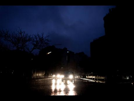 """Cars drive through an unlit street during a blackout in Buenos Aires, Argentina, Sunday, June. 16, 2019. A massive blackout left tens of millions of people without electricity in Argentina, Uruguay and Paraguay on Sunday in what the Argentine president called an """"unprecedented"""" failure in the countries' power grid. (AP Photo/Tomas F. Cuesta)"""