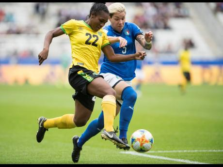 Jamaica's Mireya Grey (left) is tackled by Elena Linari of Italy as she dribbles to goal during the teams' second Group C match in the FIFA Women's World Cup at Stade Auguste-Delaune in Reims, France, on Friday, June 14. The Reggae Girlz lost 5-0.