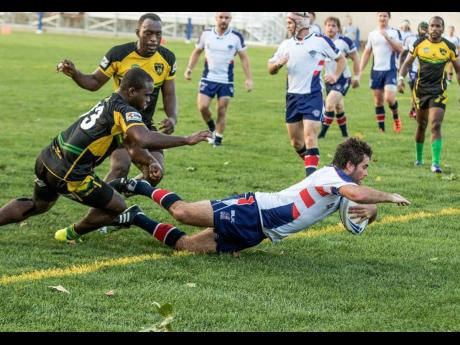 The Reggae Warriors' Leon Thomas (left) and Jermaine Pinnock (second left) attempt to prevent the USA Hawks from scoring a try during a recent rugby league game in Florida.