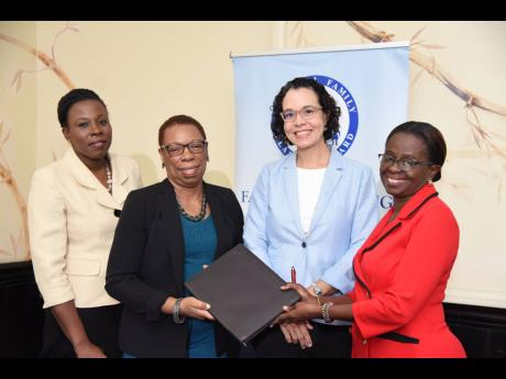 Executive Director Lovette Byfield (right) and Director General Carol Coy (second left) hold signed copies of documents for the 2019 Reproductive Health Survey with National Family Planning Board board member, Dr Diana Thorburn (second right), and Statistical Institute of Jamaica Legal Officer, Gillian Johns (left); following the signing ceremony at the Courtleigh Hotel in New Kingston last week.