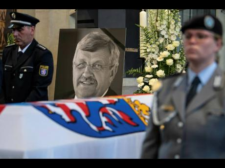 In this June 13, 2019 file photo, a picture of Walter Luebcke stands behind his coffin during the funeral service in Kassel, Germany. German authorities say they have arrested a 45-year-old man in connection with their investigation into the slaying of a regional official from Chancellor Angela Merkel's party.