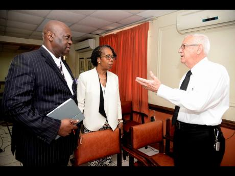 Opposition Spokesperson on Education Ronald Thwaites (right) makes a point to his deputy, Micheal Stewart, and Elaine Foster Allen, chairman of the People's National Party's Education Commission, at a press conference yesterday.