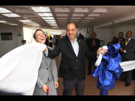 Minister of Foreign Affairs and Foreign Trade Senator Kamina Johnson Smith reacts as Senator Don Wehby, chairman of the 8th Biennal Jamaica Diaspora Conference, assists by ripping the cloth at the ribbon-cutting ceremony to officially open the marketplace at the Jamaica Conference Centre yesterday.