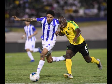 Jamaica's Dever Orgill (right) battles with Honduras defender Henry Figueroa for ball possession during their Concacaf Gold Cup match at the National Stadium on Monday night.