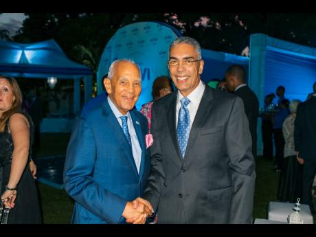 Congrats on your golden anniversary! Newly appointed head of the Bank of Jamaica, Richard Byles (right), congratulates founder and chairman of the ICWI Group, Dennis Lalor, OJ, at ICWI's 50th anniversary celebration, held at the Devon House East Lawn on June 15.