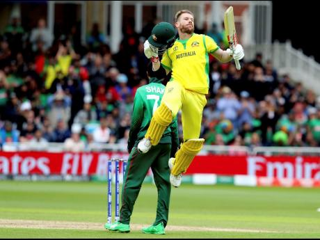 Australia's David Warner leaps into the air to celebrate scoring a century during their ICC World Cup match against Bangladesh at Trent Bridge in Nottingham, England, yesterday.
